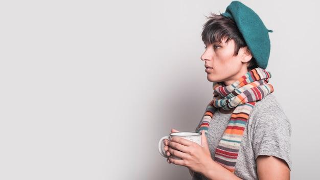 Вид сбоку серьезная молодая женщина с кружкой кофе на сером фоне
