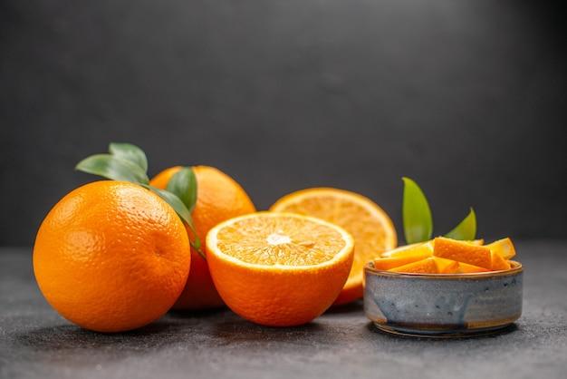 暗いテーブルの上の黄色の全体とみじん切りのオレンジのセットの側面図