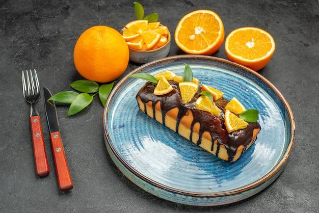 フォークとナイフで黄色の全体とカットオレンジのおいしいケーキのセットの側面図