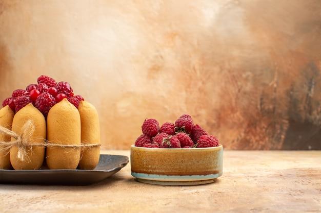 Вид сбоку на сервированный стол с подарочным тортом и фруктами для гостей на смешанном цветном столе