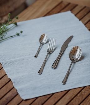 Вид сбоку набора с ложкой вилкой и ножом на скатерть на деревянном столе