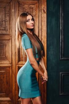 Сексуальная брюнетка модель с красивыми длинными волосами в стильном синем костюме, вид сбоку