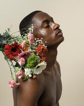 Вид сбоку человека без рубашки, позирующего с букетом цветов