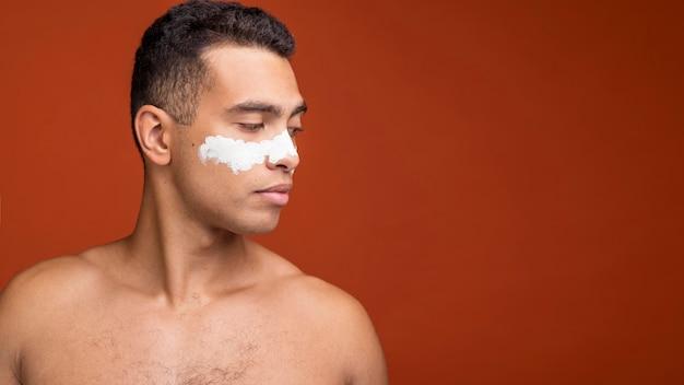 フェイスマスクとコピースペースで上半身裸の男の側面図
