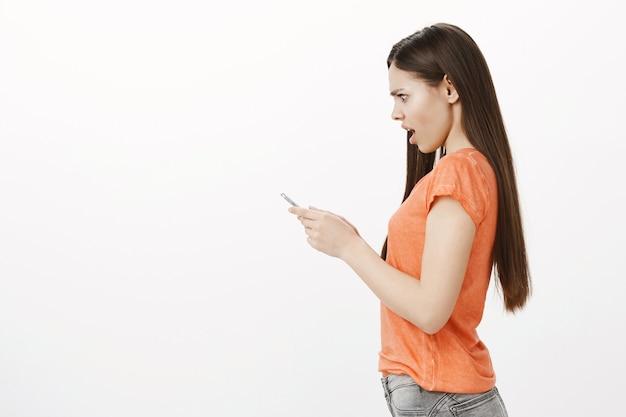 Вид сбоку потрясенной и встревоженной девушки, уставившейся на экран мобильного телефона с обеспокоенным взглядом