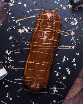Вид сбоку одного эклера с шоколадом на деревянной поверхности