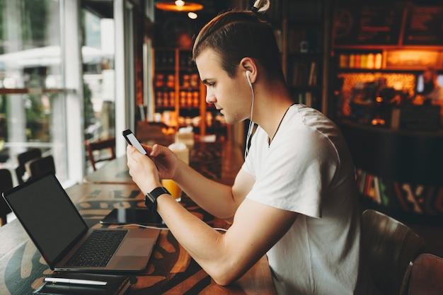 夏のシャツの創造的なヘアカットと手で携帯電話の画面にイヤホンのテキストメッセージを持つ窓の若い魅力的な男の高い木製のテーブルに座って側面図