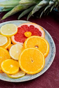 Вид сбоку нарезанные цитрусовые как лимон мандарин грейпфрут кумкват в тарелку с ананасом на фоне ткани бордо