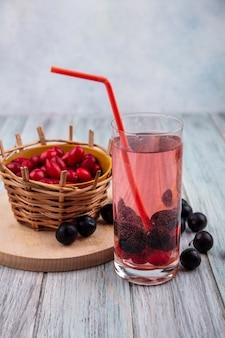 Вид сбоку небольших кислых красных ягод кизила на ведре на деревянной кухонной доске с ягодным соком кизила и терновником на сером деревянном фоне