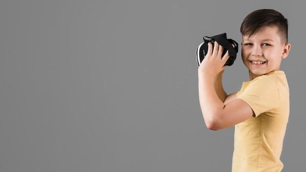 Вид сбоку смайлик мальчик держит гарнитуру виртуальной реальности с копией пространства
