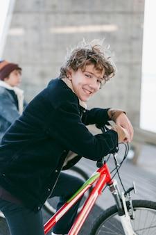 그들의 자전거와 함께 도시에서 야외에서 웃는 소년의 측면보기