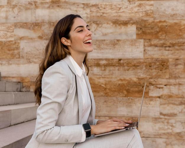 야외에서 노트북에서 작업하는 smartwatch와 웃는 사업가의 측면보기