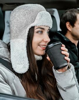 Улыбающаяся пара, наслаждающаяся теплым напитком в машине во время поездки, вид сбоку