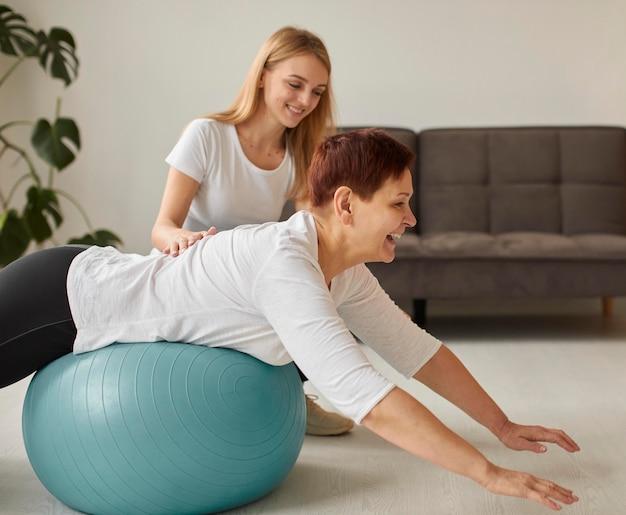 공 운동을하는 covid 회복에 웃는 노인 여성의 측면보기