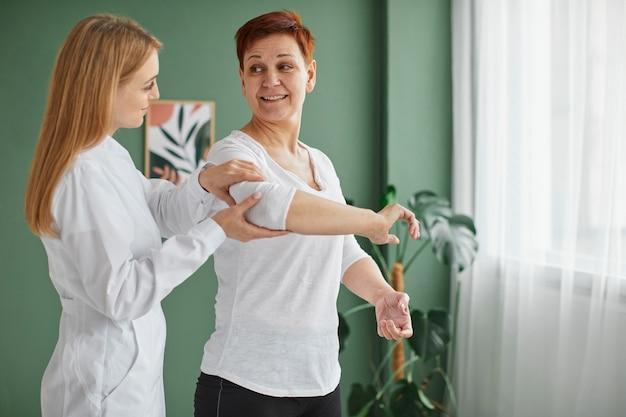 간호사와 신체 운동을하는 covid 회복에 웃는 노인 여성의 측면보기