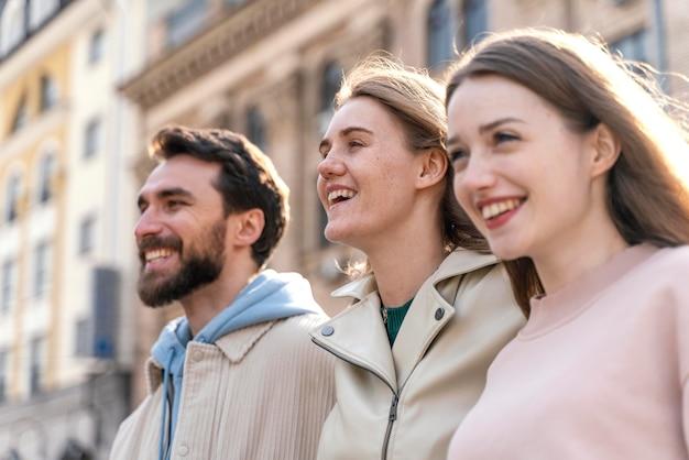도시에서 야외에서 웃는 친구의 측면보기