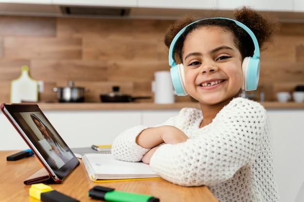Улыбающаяся маленькая девочка во время онлайн-школы с планшетом и наушниками, вид сбоку