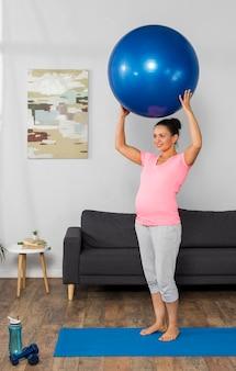 マットにボールとホームトレーニングで笑顔の妊婦の側面図