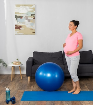 ボールで自宅トレーニングで笑顔の妊婦の側面図