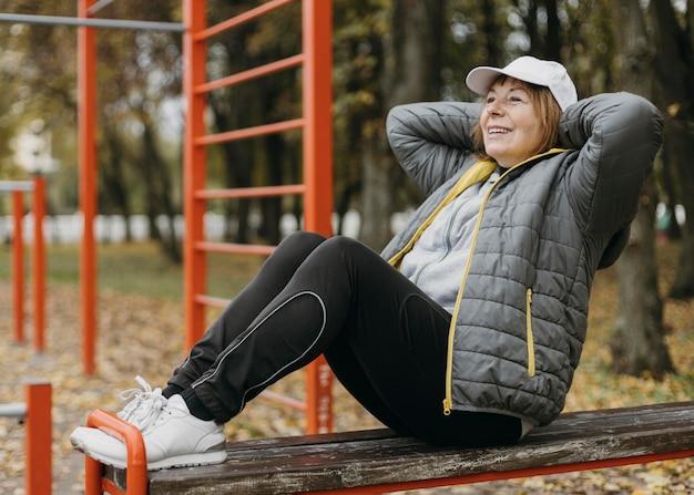 屋外で運動する笑顔の年配の女性の側面図