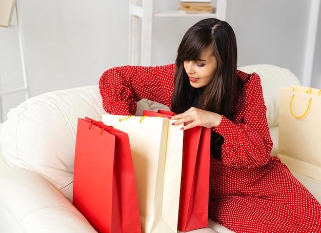 그녀가 판매 쇼핑하는 동안받은 항목을 확인하는 웃는 여자의 측면보기