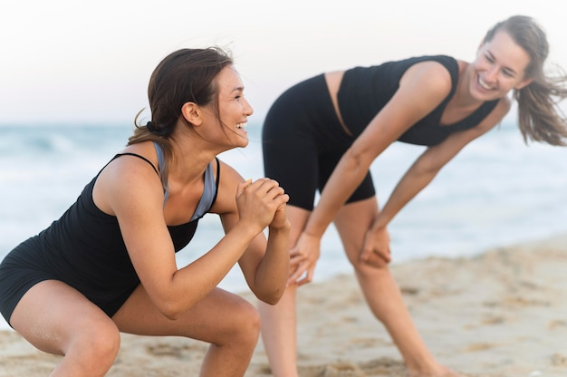 ビーチでスクワットをしている笑顔の女性の側面図