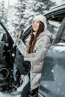 Улыбающаяся женщина, наслаждающаяся снегом во время поездки, вид сбоку