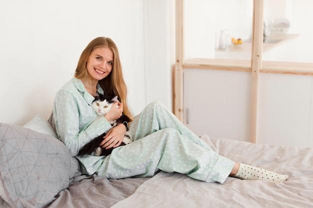 猫を保持しているベッドの上のパジャマでスマイリー女性の側面図