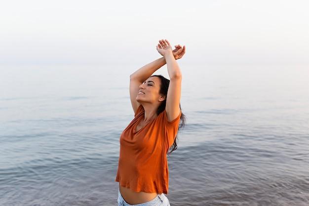 Вид сбоку смайлик женщина позирует на пляже