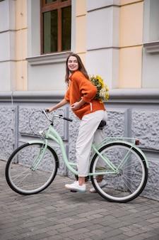 꽃의 꽃다발과 함께 야외에서 그녀의 자전거를 타고 웃는 여자의 측면보기