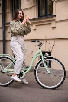 Смайлик женщина с помощью смартфона на велосипеде, вид сбоку