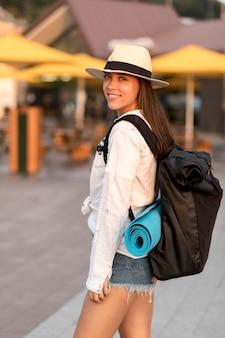 旅行中にバックパックを運ぶ帽子とスマイリー女性の側面図