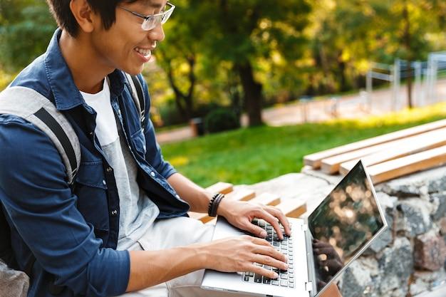 公園のベンチに座っている間ラップトップコンピューターを使用して眼鏡で笑顔のアジア人男性学生の側面図