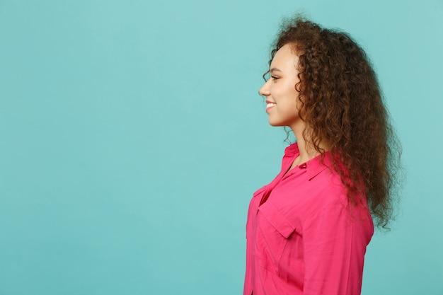 スタジオで青いターコイズブルーの壁の背景に分離して立っているピンクのカジュアルな服を着て笑顔の魅力的なアフリカの女の子の側面図。人々の誠実な感情、ライフスタイルのコンセプト。コピースペースをモックアップします。