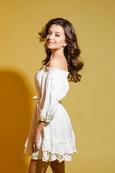 夏のドレスを着て、黄色の背景にスタジオに立って笑顔の美しい女性の側面図。ファッション。ショッピング。夏のコンセプト