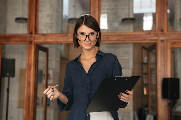Вид сбоку улыбается деловая женщина в очках