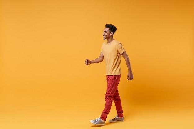 Вид сбоку улыбающегося веселого молодого афро-американского парня в повседневной одежде, позирующем изолированном на желтом оранжевом стенном портрете. концепция образа жизни искренние эмоции людей.