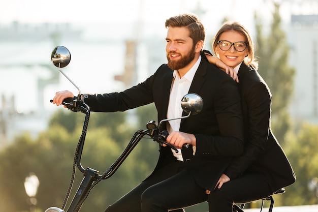 Вид сбоку улыбающейся пары в костюмах едет на мотоцикле