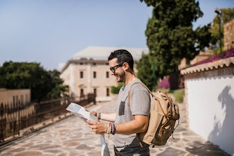Side view of smiling man looking at map standing on street