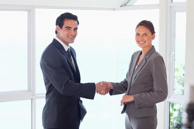 Вид сбоку улыбается торговый партнер, рукопожатие