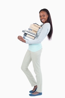 Side view of smiling woman carrying a stack of books against a white background