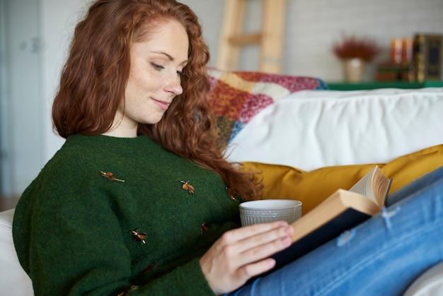 Вид сбоку улыбается женщина, читающая книгу в зимний день