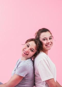 Вид сбоку улыбается молодая сестра, сидя спиной к спине на розовом фоне