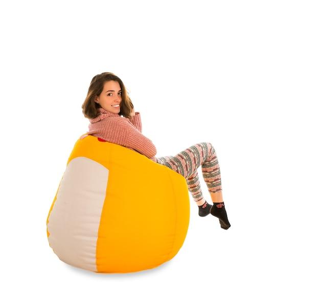 白で隔離のリビングルームまたは他の部屋の黄色のお手玉の椅子に座って笑顔の若い女性の側面図