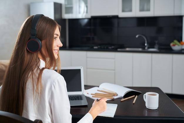 Вид сбоку улыбающейся молодой женщины в современных наушниках во время онлайн-обучения на ноутбуке