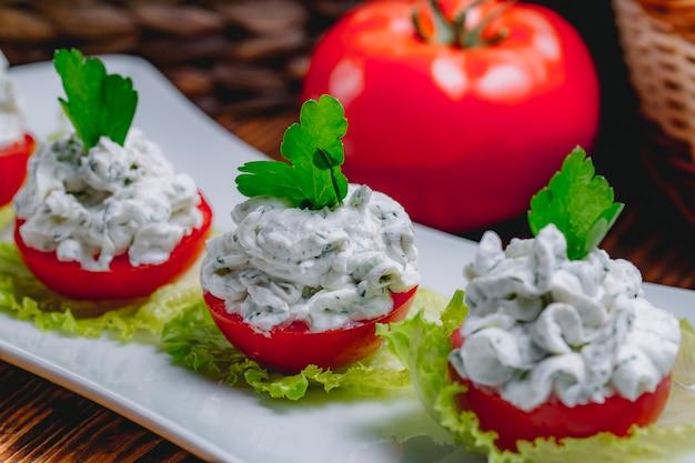Вид сбоку из сметанного йогурта с огурцами галичой и зеленью на свежих помидорах, увенчанных петрушкой на тарелке