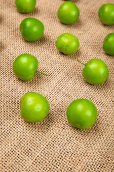 Вид сбоку кислые зеленые сливы, изолированные на столе вретище