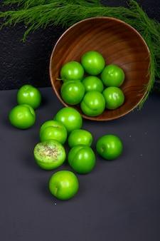 블랙 테이블에 나무 그릇에서 흩어져 신 녹색 자두의 측면보기
