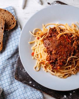 Вид сбоку спагетти болоньезе на белой тарелке на деревянной разделочной доске