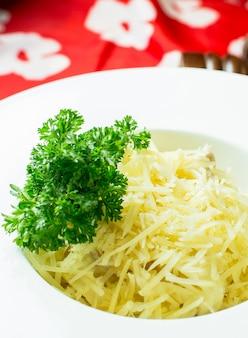 カラフルな白いボウルにパルメザンチーズのミートソースの側面図